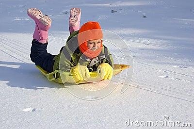 Girl Sledding on Snow Covered Lake