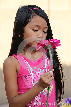 Girl Smelling Pink Daisy Flower