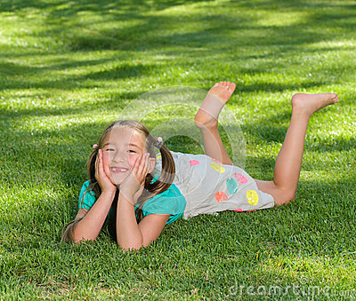 Girl Smiles Laying on Grass