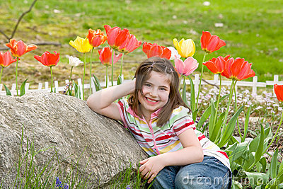 Girl Smiling in Front of Flowers