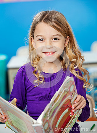 Girl Smiling While Holding Book In Kindergarten
