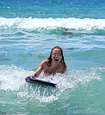 Free Girl Smiling While Riding A Big Blue Wave On A Body Board On The Blue Sea On A Sunny Day. Royalty Free Stock Photography - 125057