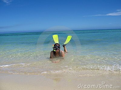 Girl snorkels at the beautiful tropical beach