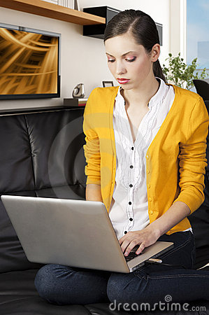 Girl on sofa with laptop, she indicates the displa