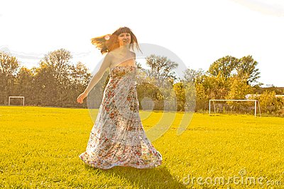 Girl spinning by sunset in the field