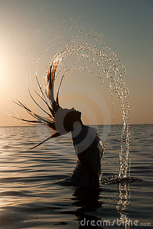 Girl splashing the sea water with her hair