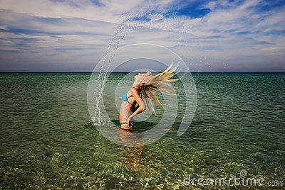 A girl splashing the sea water with her hair