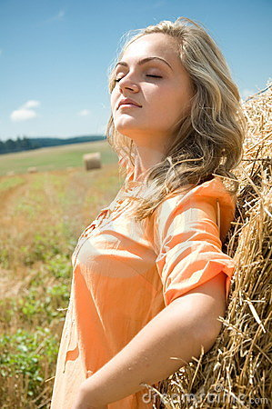 Girl at a stack of straw