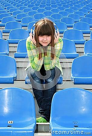 Girl at the stadium listening music