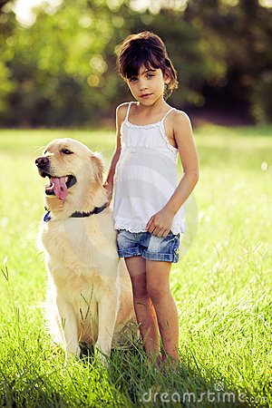 Girl standing in grass with golden retriever