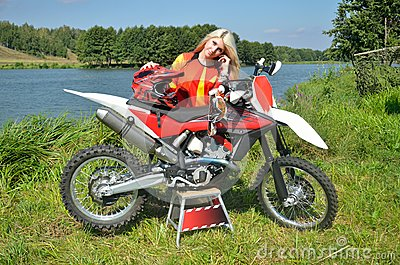 Girl is standing leaned on the motorbike