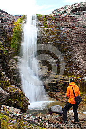 Girl standing near the beautiful waterfall and and looking at it