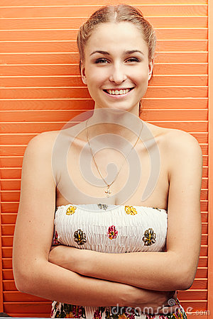 Girl standing near the orange and smiling
