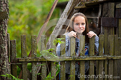 Girl standing near vintage rural fence