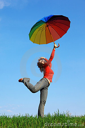 Girl standing on one leg with colorful umbrellas