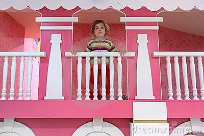 Girl standing on pink childish balcony
