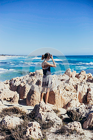 Girl Standing On Rock Formations With Hand Covering Eyes From Sun Light Near Body Of Water Free Public Domain Cc0 Image