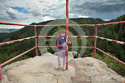 Girl standing on top of rock