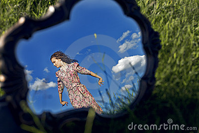 Girl stands on background sky reflected in mirror