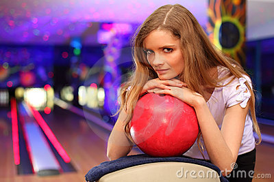 Girl stands and bases on ball in bowling club