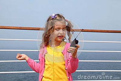 Girl stands on board ship holds portable radio