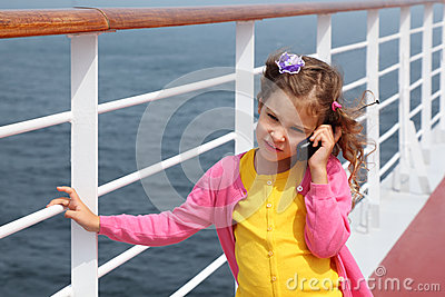 Girl stands on board ship, talks by portable radio