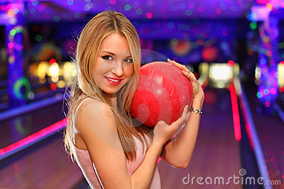 Girl stands and hugs ball in bowling club