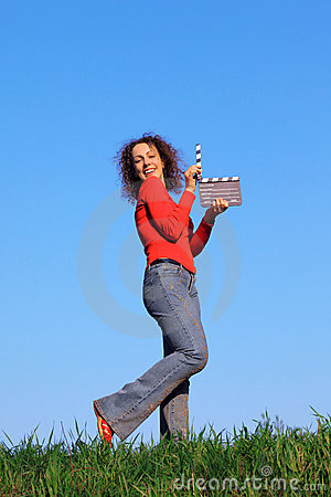Girl stands in meadow with clapperboard