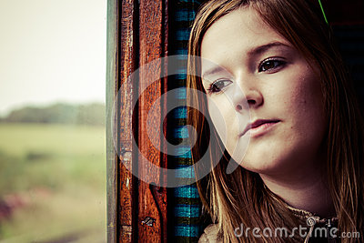 Girl staring trough a window while travelling by train