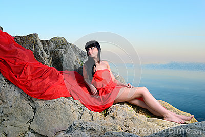 The girl on stones in a red fabric