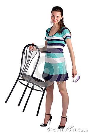Girl in stripy blue dress holds stool.