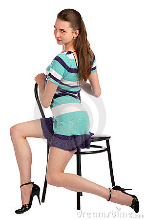 Girl in stripy blue dress sit on stool turned.