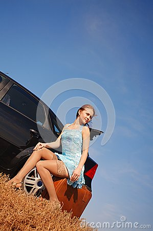 Girl with suitcase near the car