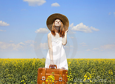 Girl with suitcase at spring rapeseed field.