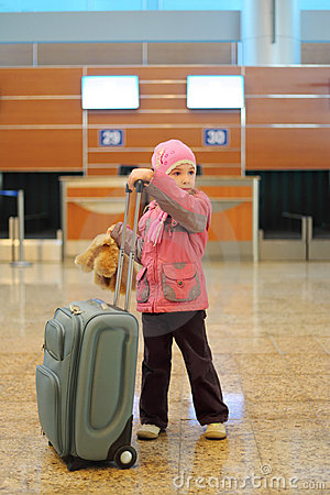 Girl with suitcase standing alone at airport
