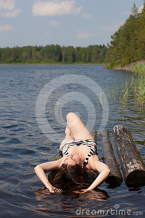 The girl sunbathes on a raft