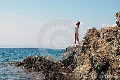 Girl sunbathes on a rock