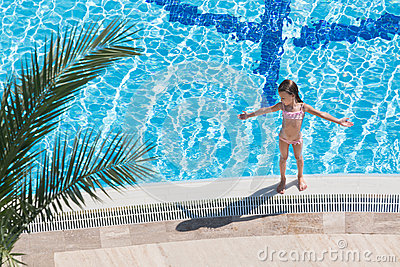 Girl sunbathing on the edge of the pool
