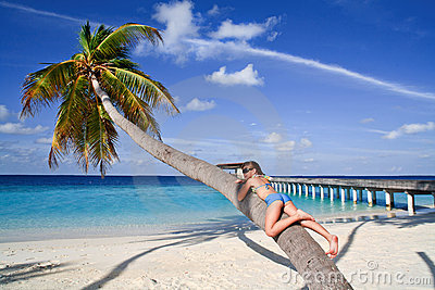Girl sunbathing on a palm
