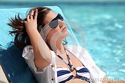 Girl sunbathing by the pool