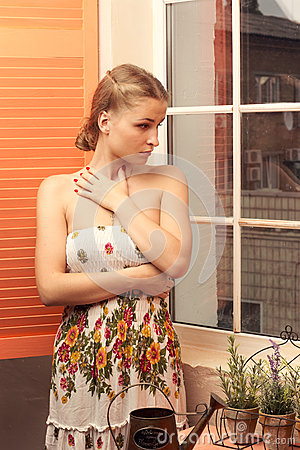 Girl in sundress near  window with flowers