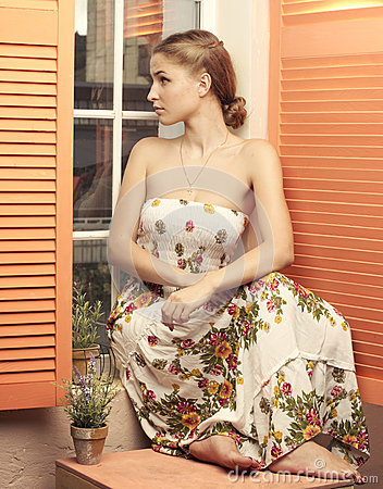 Girl in sundress sitting and looking out window