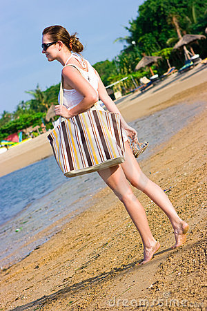 Girl with sunglasses and bag on the beach