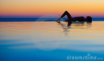 Girl in Sunset infinity pool