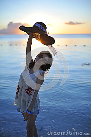 Girl in sunset with a straw hat