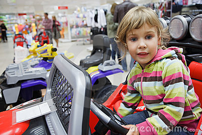 Girl in supermarket alone in department of toys