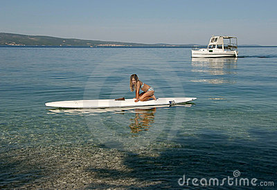 Girl with surf desk and boat