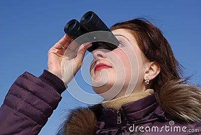 Girl with surprised looks through binoculars