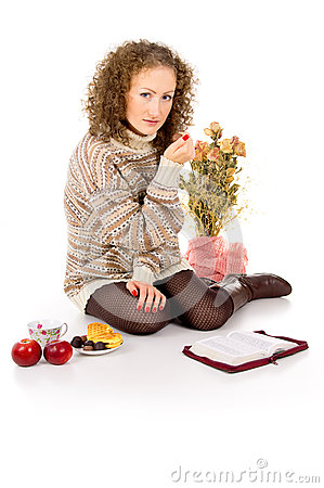 Girl in a sweater with a book and eating candy