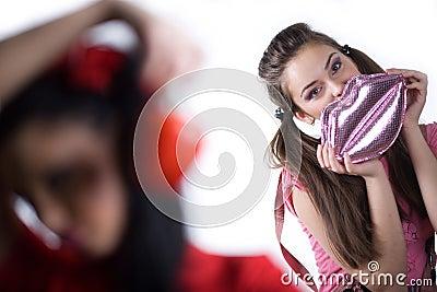 Girl with sweet pepper and nice girl with handbag